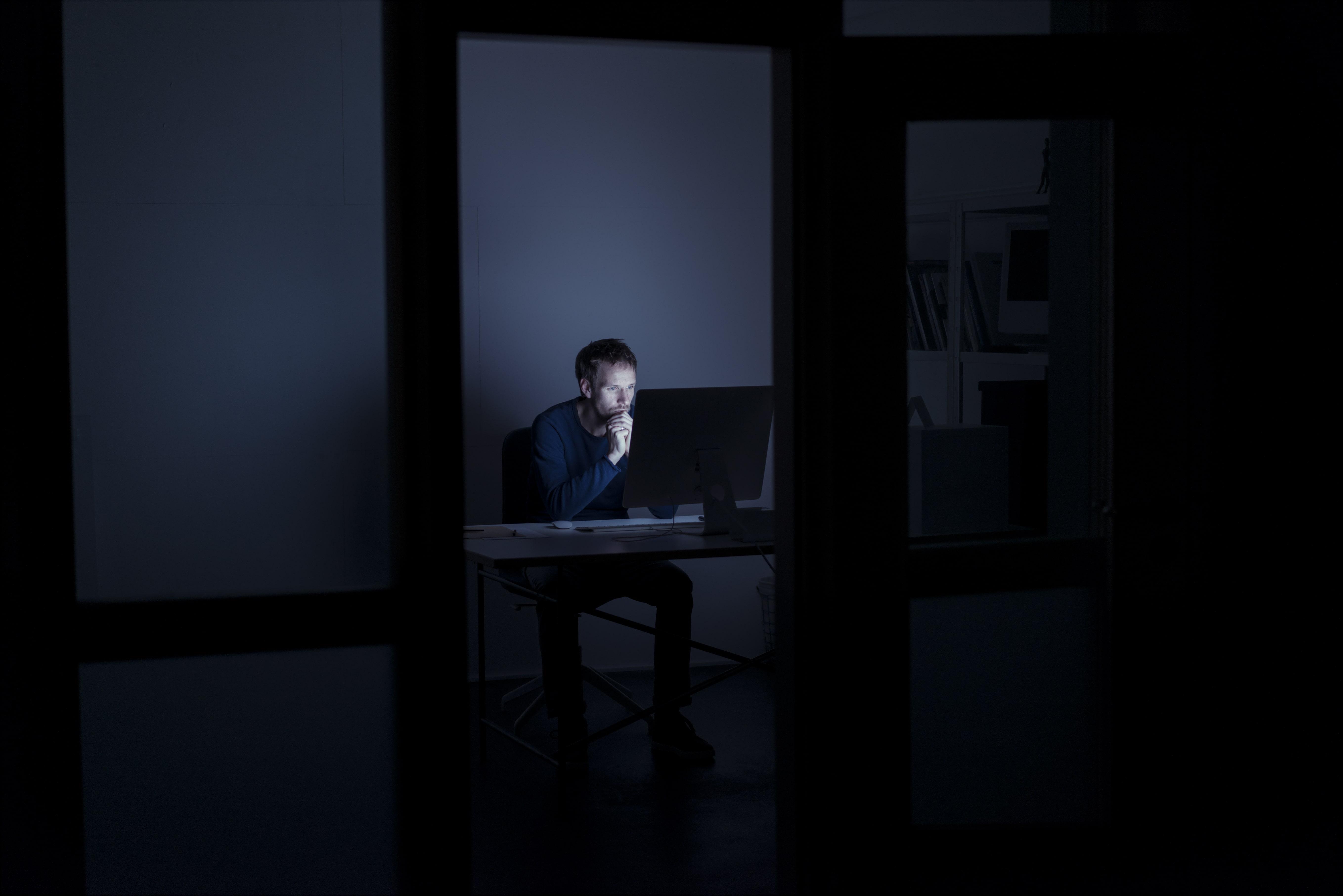 Ein Mann sitzt vor einem Rechner im Home-Office, im Zimmer gibt es bis auf den Bildschirm keine Lichtquelle.