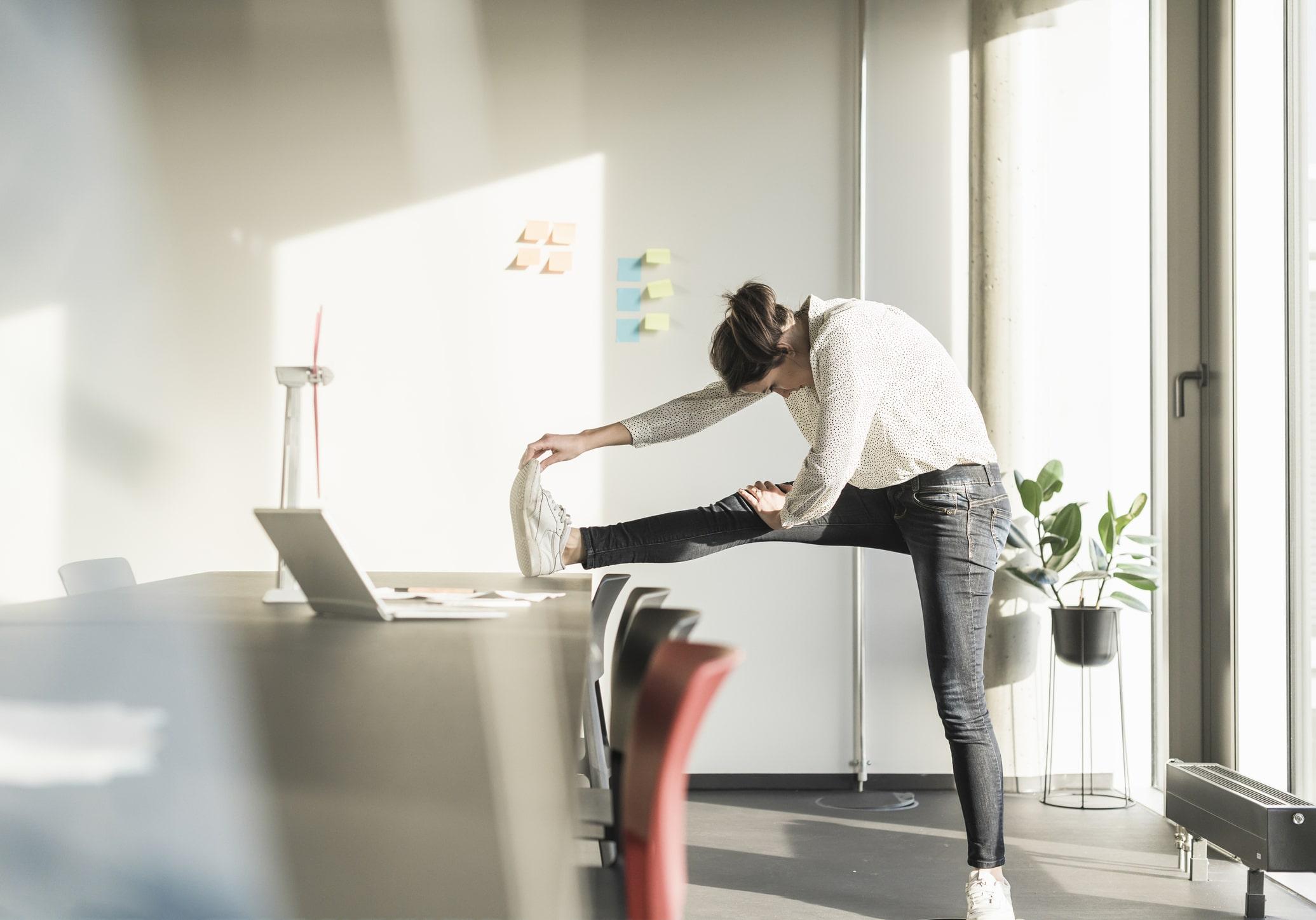 Eine Frau stellt einen Fuß auf ihrem Schreibtisch ab, beugt sich mit Kopf und Rücken weit nach vorne, um sich zu dehnen und bewegen.