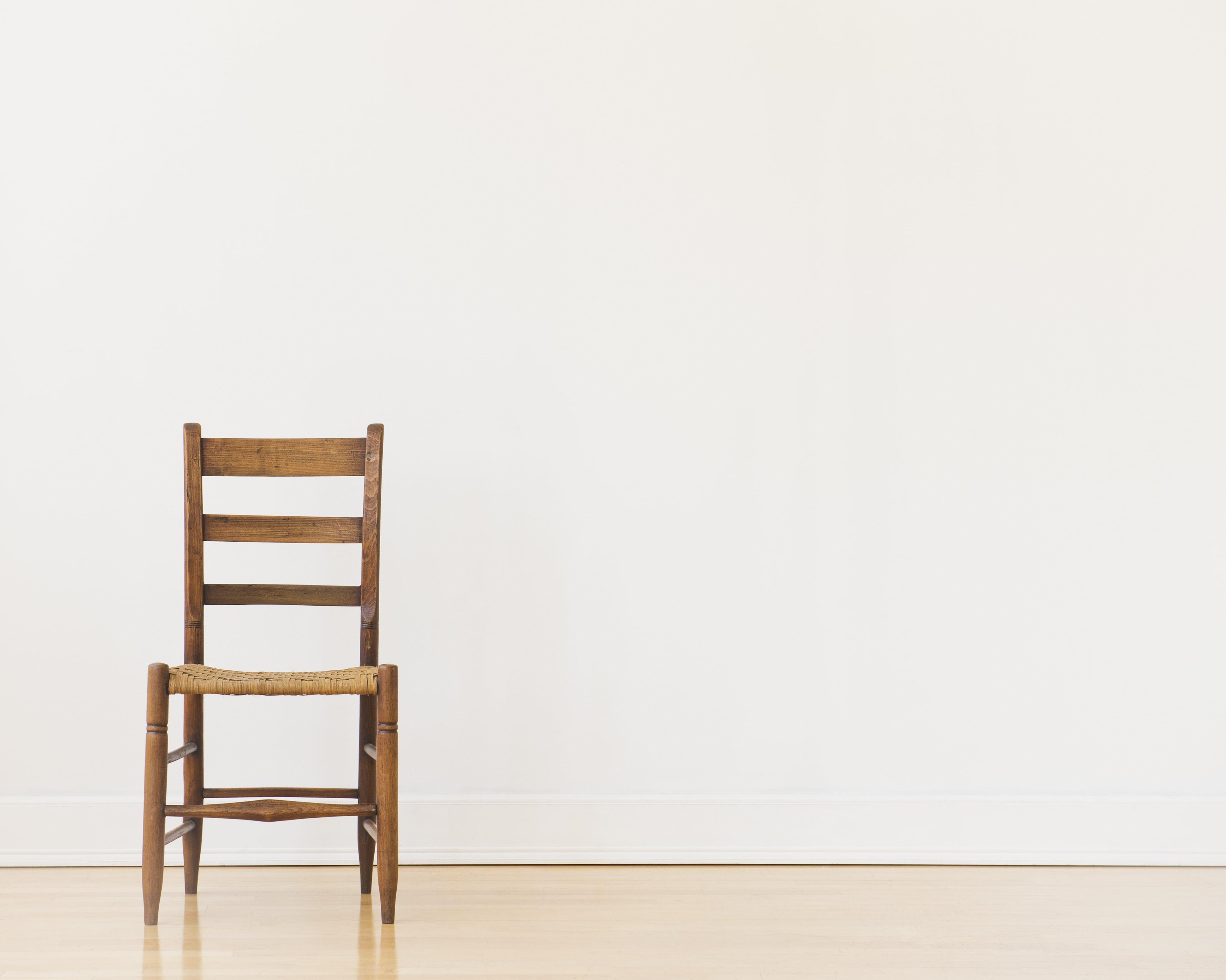Die Aufnahme zeigt einen Holzstuhl, der an einer Wand steht. Der Stuhl ist nicht für die lange Arbeit am Schreibtisch geeignet.