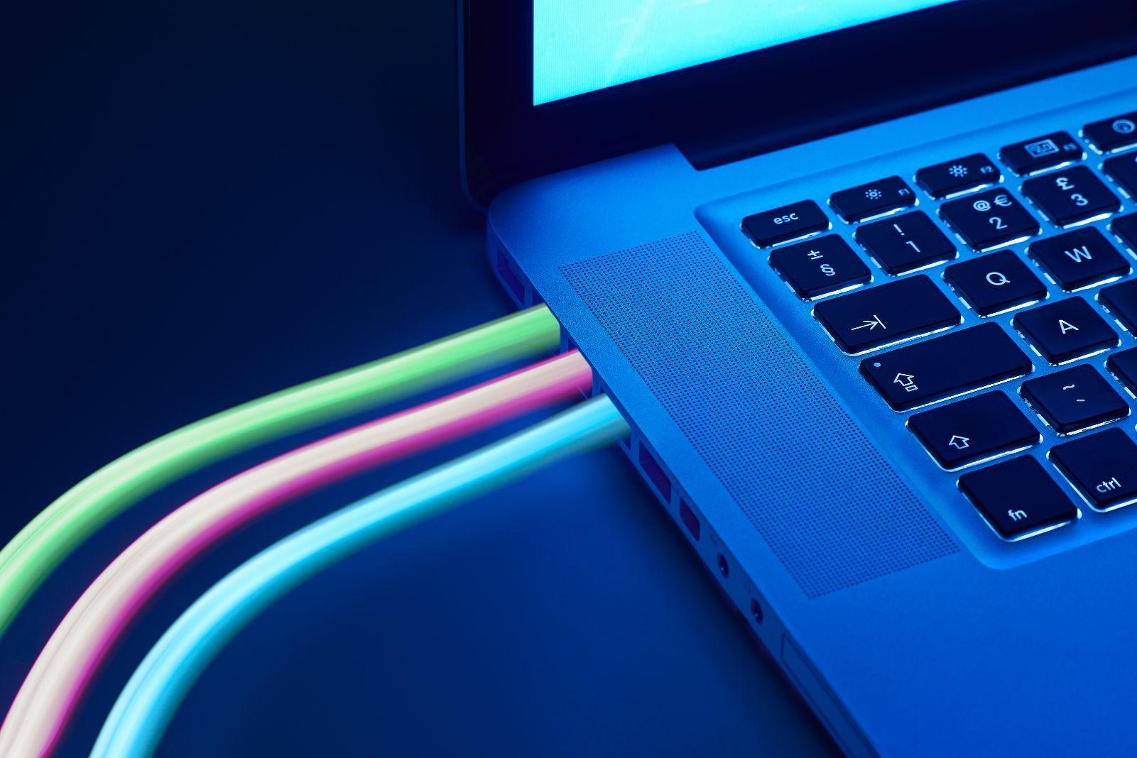 Man sieht ein Laptop/Macbook bei Nacht mit mehreren, verbundenen Kabeln