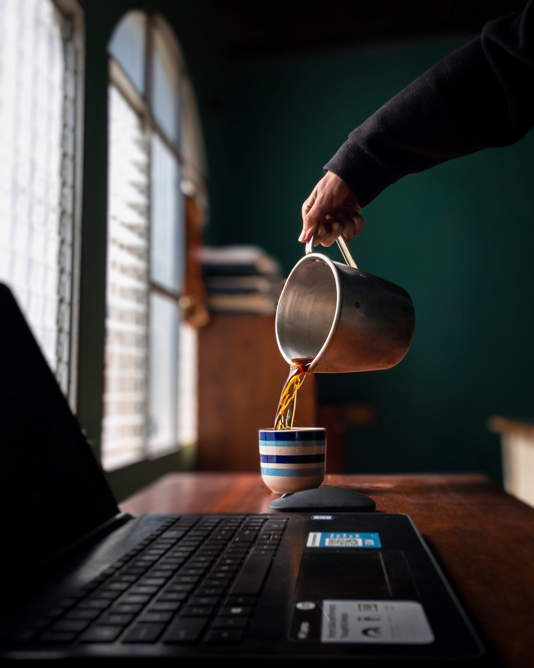 Ein Mann gießt Kaffee in eine Tasse die neben seinem Laptop auf dem Schreibtisch stehtEin Mann gießt Kaffee in eine Tasse die neben seinem Laptop auf dem Schreibtisch steht