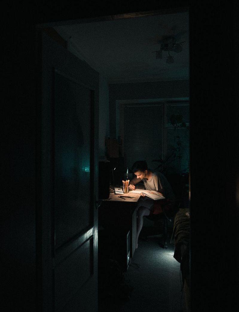 Ein Mann sitzt alleine in der Dunkelheit vor seinem Schreibtisch und arbeitet